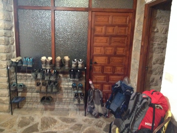 Backpacks, shoes, and poles in the Obanos albergue entrance, waiting for their owners to finish breakfast