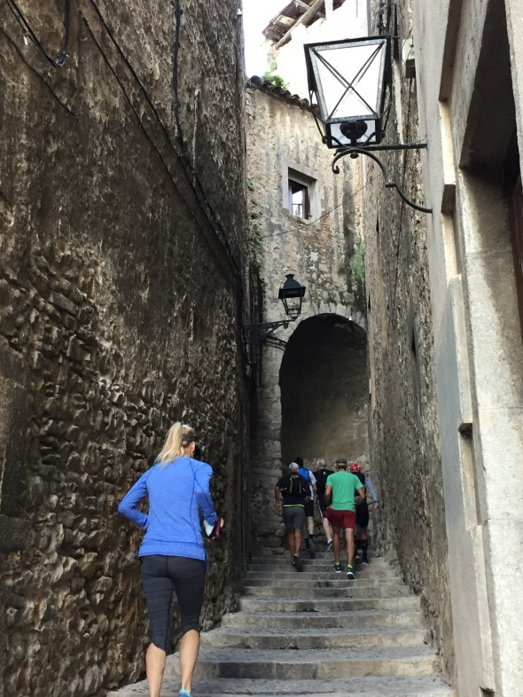 The back of Sally Anderson and the rest of our running group ascending a stone staircase in the heart of Girona