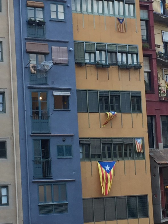 "The Catalonia Independence flag hangs outside many windows and homes around here.  The ""regular"" flag of the area of Catalonia just has the stripes; this one that proclaims their desire for independence from the country has the blue triangle and star."